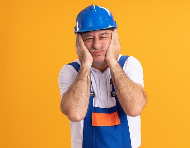 Zirytowany dorosły kaukaski mężczyzna budowniczy w mundurze kładzie ręce na twarzy na pomarańczowo