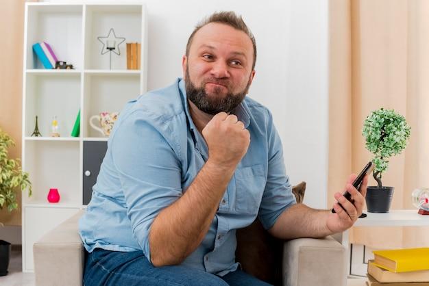 Zirytowany dorosły słowiański mężczyzna siedzi na fotelu, trzymając pięść i trzymając telefon w salonie