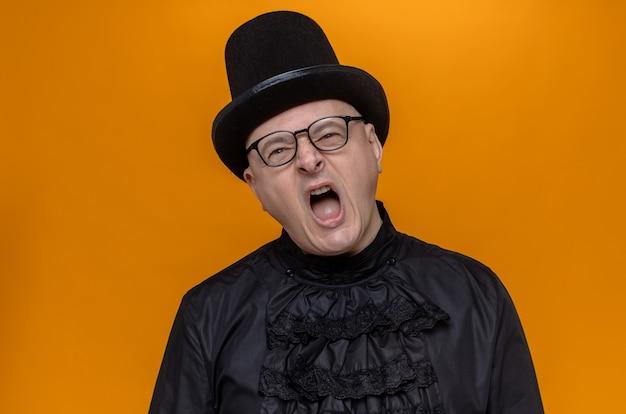 Zirytowany dorosły słowiański mężczyzna w cylindrze i okularach optycznych w czarnej gotyckiej koszuli krzyczy na kogoś patrzącego z przodu