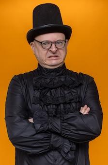 Zirytowany dorosły słowiański mężczyzna w cylindrze i okularach optycznych w czarnej gotyckiej koszuli stojącej ze skrzyżowanymi rękami