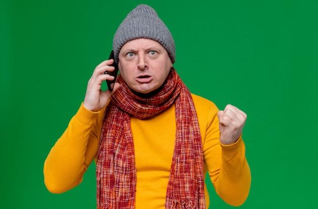 Zirytowany dorosły słowiański mężczyzna w czapce zimowej i szaliku na szyi rozmawiający przez telefon i trzymający pięść