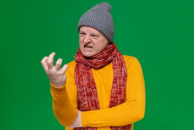 Zirytowany dorosły słowiański mężczyzna w czapce zimowej i szaliku na szyi, ściskając i patrząc na palce