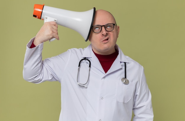 Zirytowany dorosły słowiański mężczyzna w okularach optycznych w mundurze lekarza ze stetoskopem, trzymający głośnik i przewracający oczami
