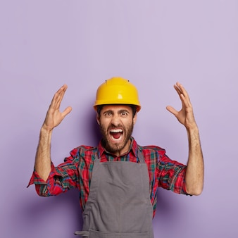 Zirytowany emocjonalny robotnik nosi żółty ochronny hełm ochronny, koszulę w kratkę i fartuch, ma dużo pracy, krzyczy ze stresu i paniki, podnosi ramiona emocjonalnie