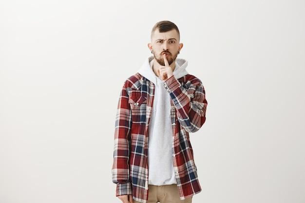 """Zirytowany hipster facet uciszający z palcem przyciśniętym do ust, powiedz """"bądź cicho"""""""