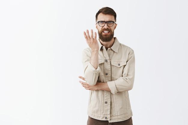 Zirytowany i sfrustrowany brodaty mężczyzna w okularach pozujący przy białej ścianie