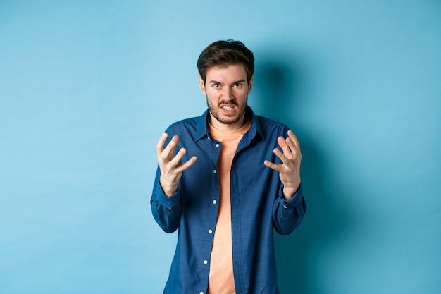 Zirytowany i wściekły mężczyzna unoszący ręce i zaciskający zęby oburzony, wkurzony wpatruje się w kamerę, zamierza kogoś zabić, stojąc na niebieskim tle.