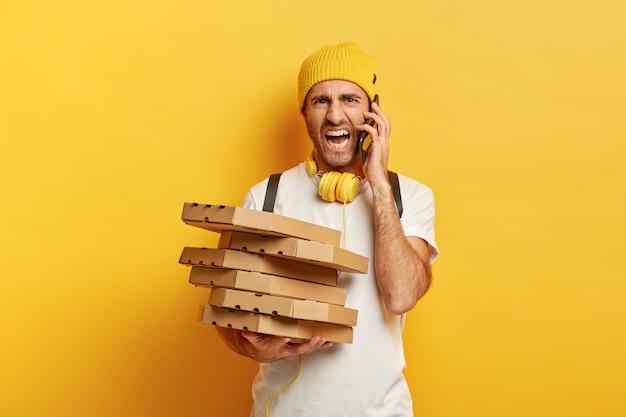 Zirytowany kurier z pudełkami po pizzy