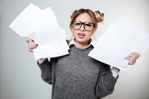 Zirytowany marszcząc brwi młoda kobieta w okularach, stojąc i trzymając dokumenty