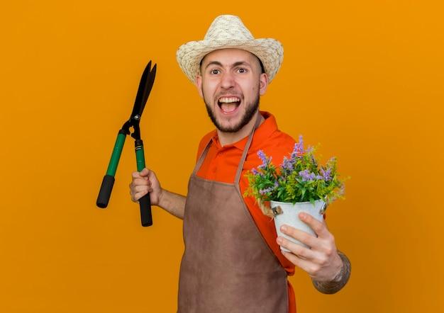 Zirytowany męski ogrodnik w kapeluszu ogrodniczym trzyma cążki i kwiaty w doniczce