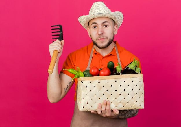 Zirytowany męski ogrodnik w kapeluszu ogrodniczym trzyma kosz warzyw i grabie
