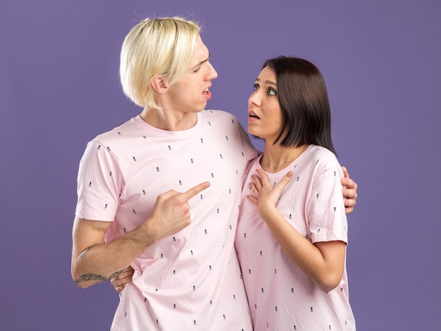 Zirytowany mężczyzna i zaniepokojona kobieta w piżamie i patrzący na siebie