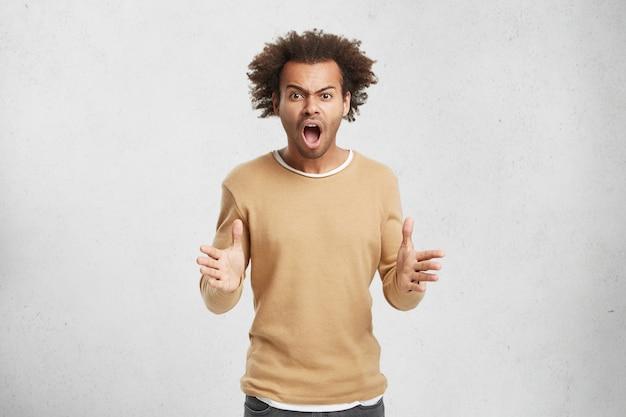 Zirytowany mężczyzna rasy mieszanej trzyma się za ręce w wściekłym geście, głośno krzyczy, podobnie jak kłótnia