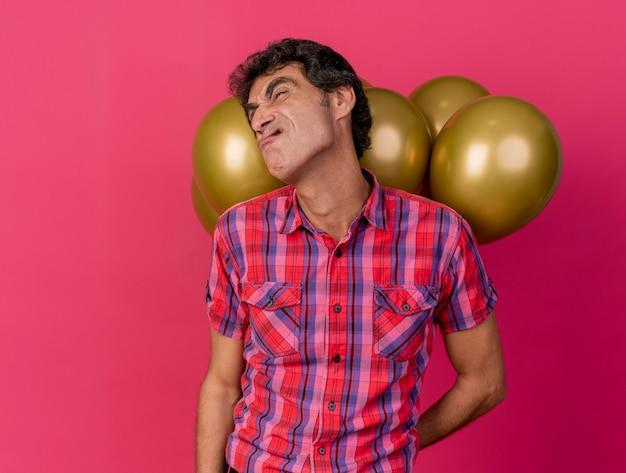 Zirytowany mężczyzna w średnim wieku kaukaski strona trzyma balony za plecami patrząc na bok na białym tle na szkarłatnym tle z miejsca na kopię