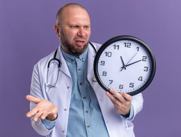 Zirytowany mężczyzna w średnim wieku, ubrany w szatę medyczną i stetoskop, trzymający i patrzący na zegar pokazujący pustą rękę odizolowaną na fioletowej ścianie