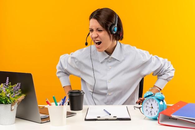 Zirytowany młoda dziewczyna call center sobie zestaw słuchawkowy siedzi przy biurku z zamkniętymi oczami na pomarańczowym tle