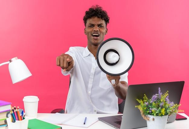 Zirytowany młody afroamerykański uczeń siedzący przy biurku z szkolnymi narzędziami trzymający głośnik i wskazujący na różowej ścianie