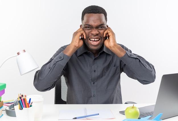 Zirytowany młody afroamerykański uczeń siedzący przy biurku z szkolnymi narzędziami zamykającymi uszy palcami odizolowanymi na białej ścianie