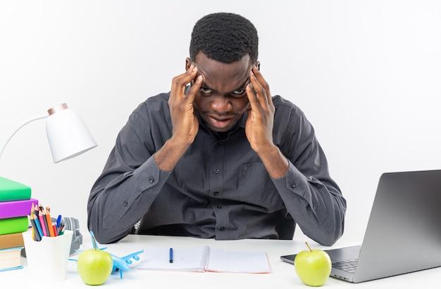 Zirytowany młody afroamerykański uczeń siedzący przy biurku ze szkolnymi narzędziami kładący ręce na jego czole