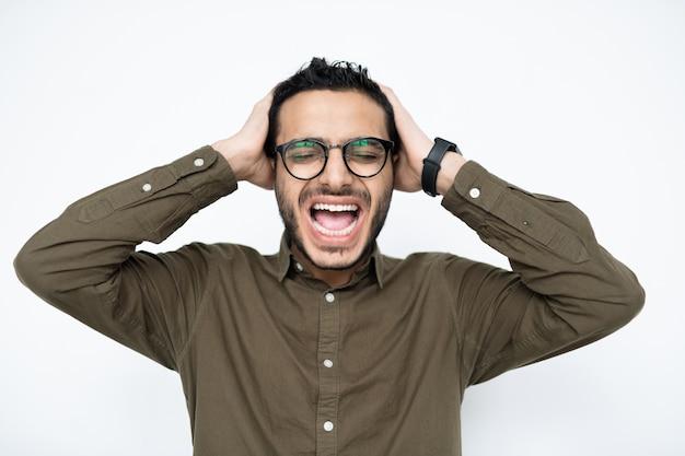 Zirytowany młody biznesmen rasy mieszanej w okularach, trzymając ręce na głowie i krzycząc w izolacji