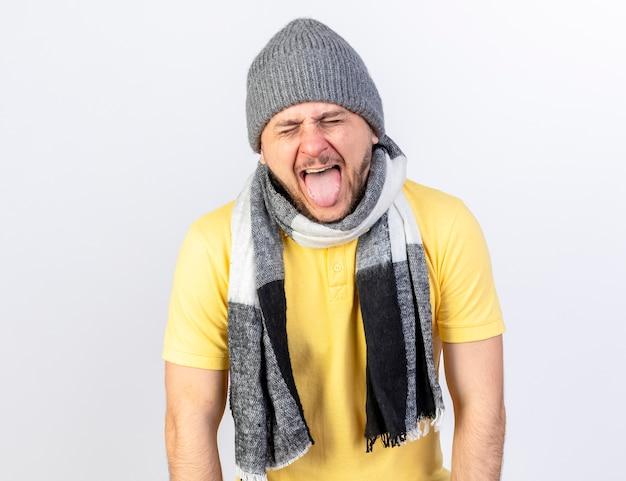 Zirytowany młody blondyn chory stoi z zamkniętymi oczami w czapce zimowej i szaliku wystającym językiem na białej ścianie