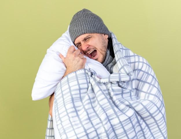Zirytowany młody blondyn chory ubrany w zimowy kapelusz zawinięty w poduszkę w kratę przytula na oliwkowej ścianie