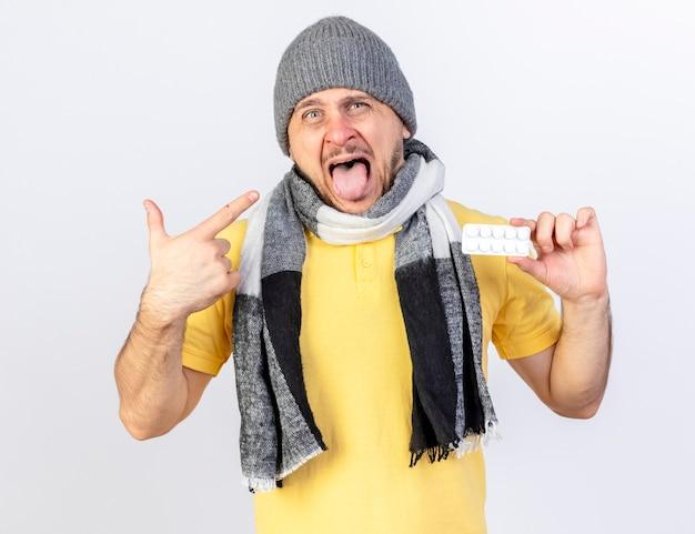 Zirytowany młody blondyn chory w czapce zimowej i szaliku trzyma paczkę tabletek medycznych i wskazuje na bok na białym tle na białej ścianie