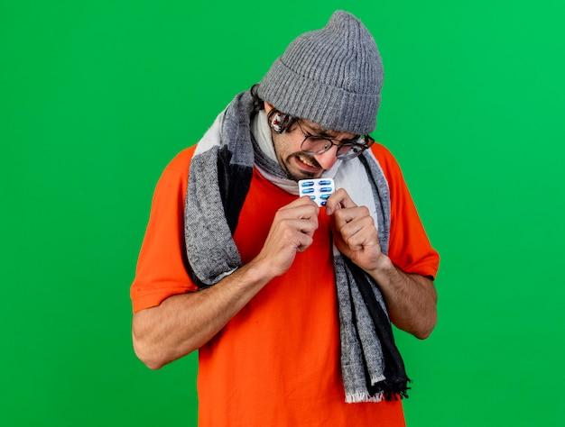 Zirytowany młody chory człowiek w okularach czapka zimowa i szalik trzymający paczkę kapsułek medycznych z paczką kapsułek pod kapeluszem odizolowanym na zielonej ścianie