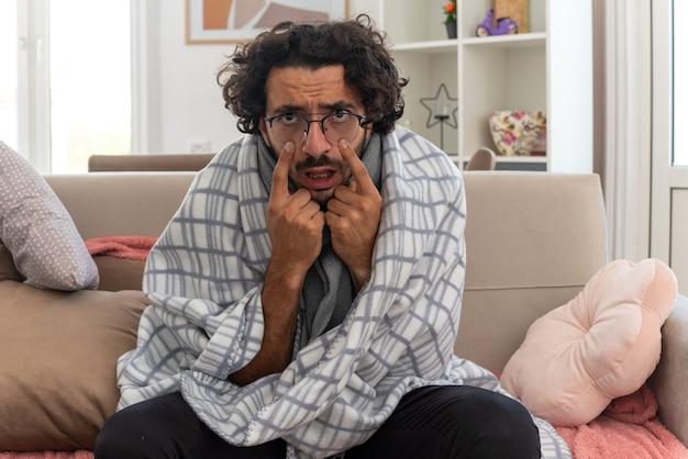 Zirytowany młody chory kaukaski mężczyzna w okularach optycznych owinięty w kratę z szalikiem na szyi podciągającym powieki siedzący na kanapie w salonie