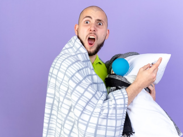 Zirytowany młody chory mężczyzna owinięty w kratę stoi bokiem trzymając poduszkę z narzędziami medycznymi na fioletowej ścianie