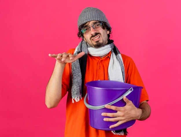 Zirytowany młody chory mężczyzna w okularach czapka zimowa i szalik trzyma plastikowe wiadro, trzymając rękę w powietrzu, patrząc na przód odizolowany na różowej ścianie z miejscem na kopię