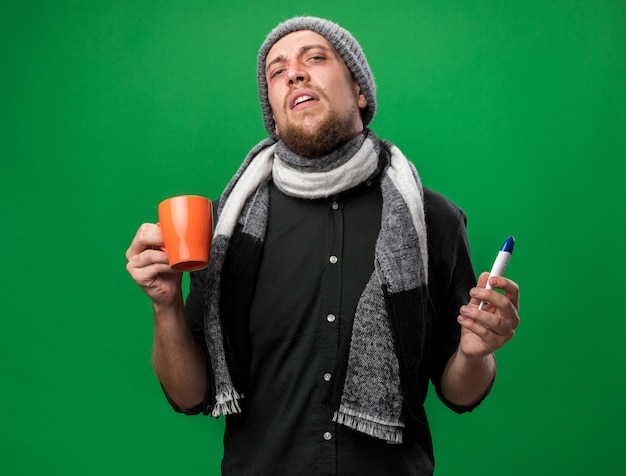 Zirytowany młody chory słowiański mężczyzna z szalikiem na szyi w czapce zimowej trzymającej termometr i kubek