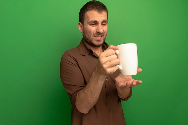 Zirytowany młody człowiek na białym tle na zielony trzymając i patrząc na filiżankę herbaty, trzymając rękę w ścianie powietrza