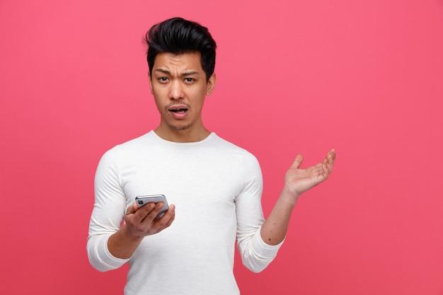 Zirytowany młody człowiek trzyma telefon komórkowy pokazuje pustą rękę