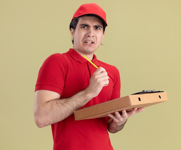 Zirytowany młody dostawca w czerwonym mundurze i czapce, trzymający schowek na opakowanie pizzy i ołówek, patrzący na przód odizolowany na oliwkowozielonej ścianie