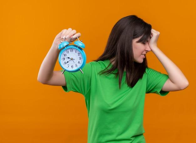 Zirytowany młody kaukaski dziewczyna w zielonej koszuli trzyma zegar i kładzie rękę na głowie na na białym tle pomarańczowym tle