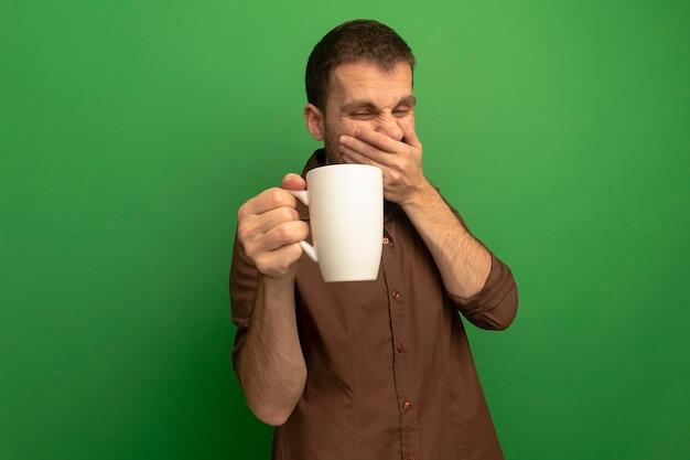 Zirytowany młody kaukaski mężczyzna na białym tle na zielony trzymając i patrząc na filiżankę herbaty, trzymając rękę na tle usta z miejsca na kopię