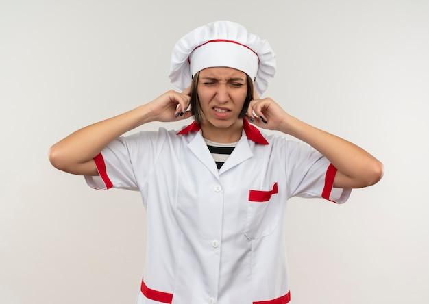 Zirytowany młody kucharz w mundurze szefa kuchni kładzie palce na uszach z zamkniętymi oczami na białym tle