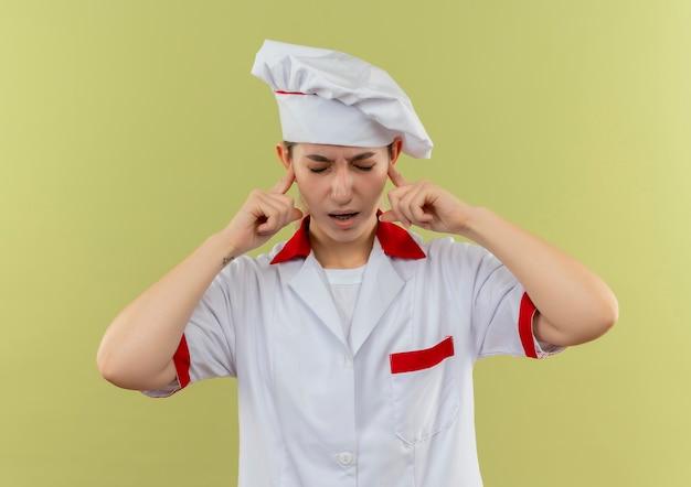 Zirytowany młody ładny kucharz w mundurze szefa kuchni wkładający palce do uszu z zamkniętymi oczami na zielonej ścianie