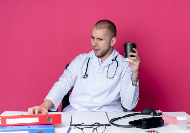 Zirytowany młody lekarz płci męskiej ubrany w szlafrok medyczny i stetoskop siedzący przy biurku z narzędziami roboczymi trzymający plastikową filiżankę kawy patrząc na biurko odizolowane na różowo