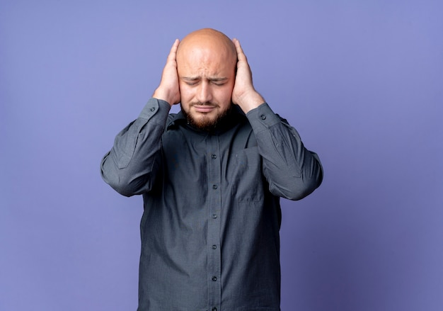 Zirytowany młody łysy mężczyzna call center kładzie ręce na uszach z zamkniętymi oczami na fioletowym tle z miejsca na kopię