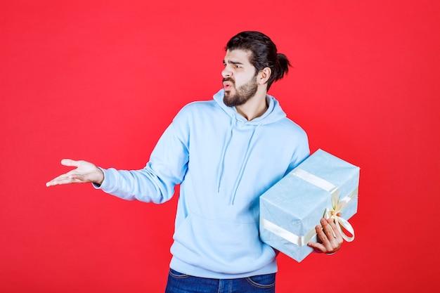 Zirytowany młody mężczyzna trzymający prezent i patrzący na prawą stronę