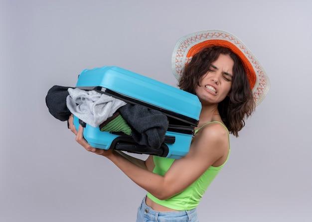 Zirytowany młody podróżnik kobieta w kapeluszu i trzyma walizkę pełną ubrań stojących w widoku profilu na odosobnionej białej ścianie
