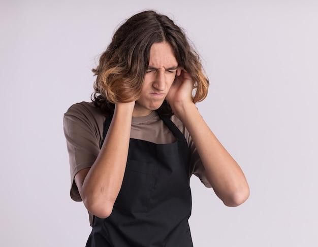 Zirytowany młody przystojny fryzjer ubrany w mundur wkłada palce do uszu z zamkniętymi oczami na białym tle na białej ścianie