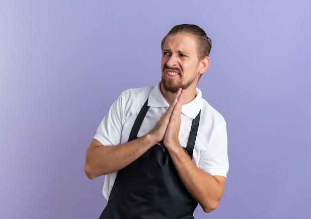 Zirytowany młody przystojny fryzjer w mundurze kładąc ręce w geście modlitwy, patrząc na bok na białym tle na fioletowo z miejsca na kopię