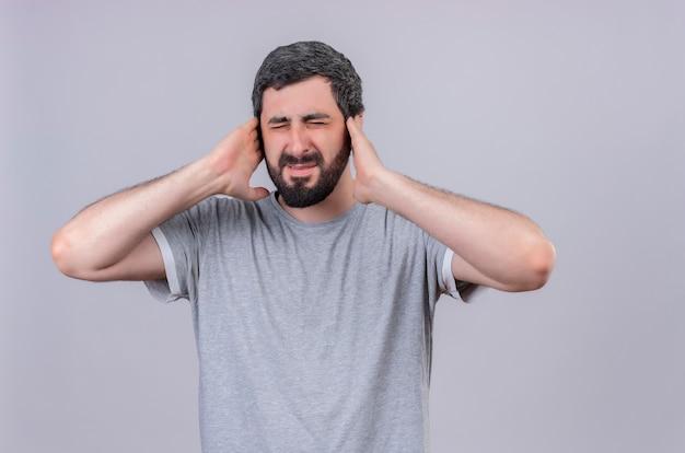 Zirytowany młody przystojny kaukaski mężczyzna wkłada ręce na uszy z zamkniętymi oczami na białym tle