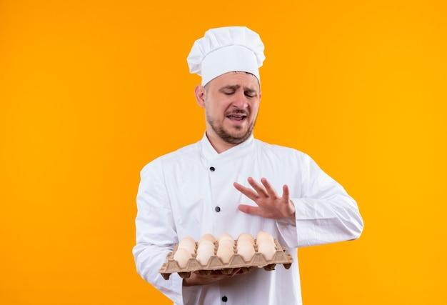 Zirytowany młody przystojny kucharz w mundurze szefa kuchni, trzymający karton z jajkami, gestykulujący nie na białym tle na pomarańczowej ścianie