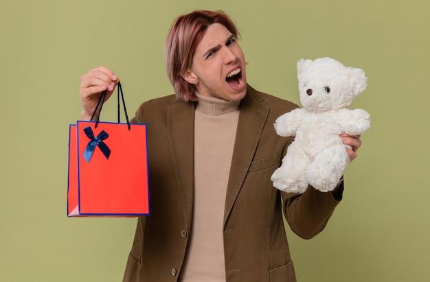 Zirytowany młody przystojny mężczyzna trzyma białego misia i torbę na prezenty patrząc na przód