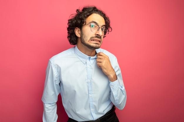 Zirytowany młody przystojny mężczyzna w okularach, patrząc na przód chwytając kołnierz koszuli na białym tle na różowej ścianie