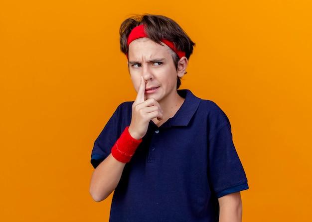 Zirytowany młody przystojny sportowy chłopiec noszący opaskę i opaski na nadgarstki z aparatami ortodontycznymi patrząc z boku kładąc palec na nosie odizolowany na pomarańczowej ścianie z miejscem na kopię